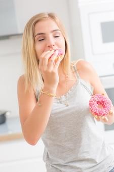 Jonge blonde meid eet roze donuts in de keuken van het huis met smaakemoties.