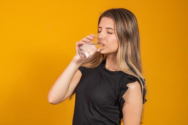 Jonge blonde meid krijgt gehydrateerd drinkwater