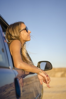 Jonge blonde meid met een zonnebril kijkt uit de auto in een woestijn in las bardenas reales, spanje