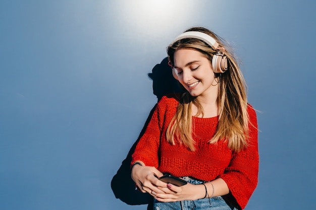 Jonge blonde meid met koptelefoon glimlacht en kijkt naar haar smartphone op blauwe achtergrond