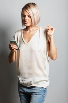 Jonge blonde meisje in spijkerbroek en een wit t-shirt met een telefoon in haar hand kijkt naar het scherm. bloggen, online communicatie en sociale netwerken.