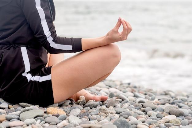 Jonge blonde meisje kijkt uit op de zee en mediteert. evenwicht en rust, ruimte voor tekst