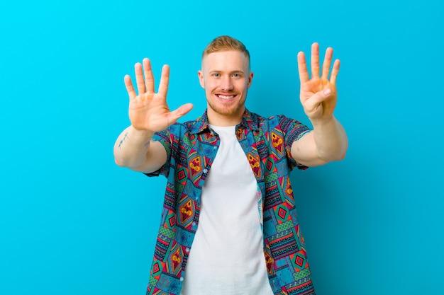 Jonge blonde mens die een en druk overhemd draagt dat vriendschappelijk glimlacht kijkt, tonend negen of negende met voorwaartse hand, aftellend