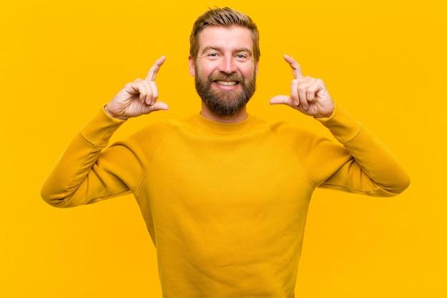 Jonge blonde mens die of eigen glimlach met beide handen ontwerpt schetst, die positief en gelukkig, wellness oranje muur kijkt