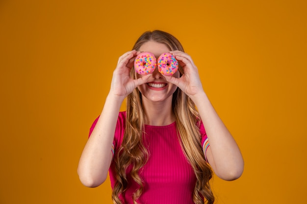 Jonge blonde met donuts op gele achtergrond.