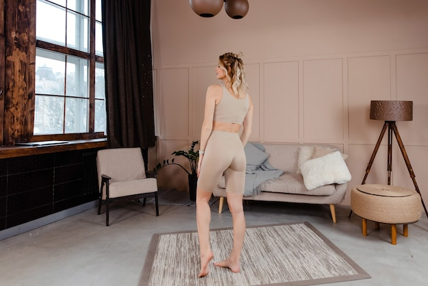 Jonge blonde met gespierde lichaamsvorm poseren op camera in lichte kamer met modern interieur