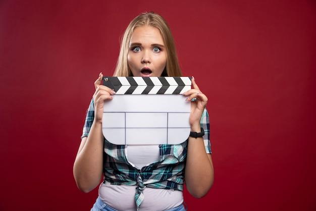 Jonge blonde model met een lege film film film klepel bord en ziet er gestrest en onervaren uit.