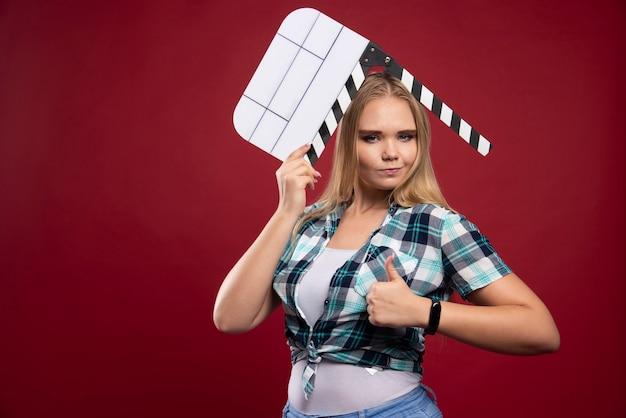 Jonge blonde model met een lege film film klepel bord en plezier.