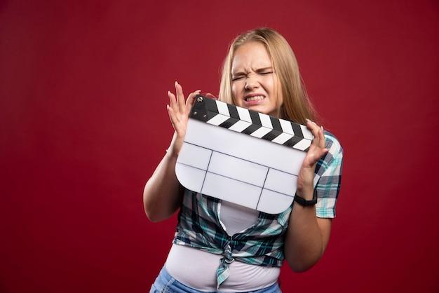 Jonge blonde model met een lege film film klepel bord en ziet er ontevreden uit.