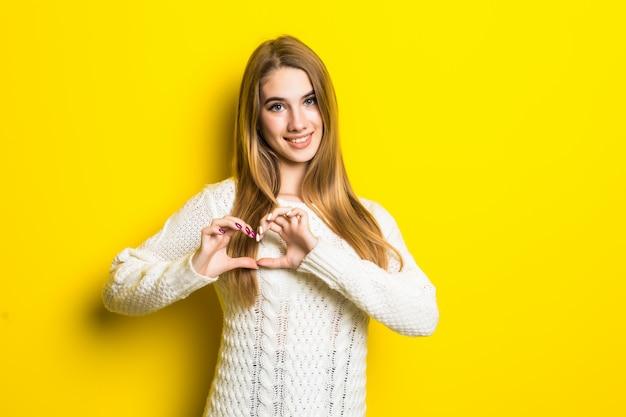 Jonge blonde model op geel is verliefd toont hartteken met haar handen