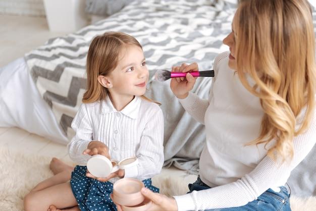 Jonge blonde moeder die een penseel vasthoudt en op het punt staat een paar slagen poeder te maken op de neus van haar dochter die nog een doos met poeder vasthoudt