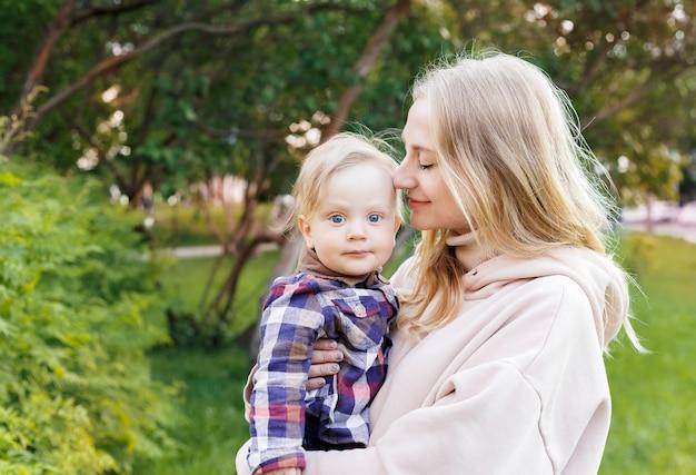 Jonge blonde moeder houdt haar zoon in haar armen, knuffelt hem zachtjes Premium Foto