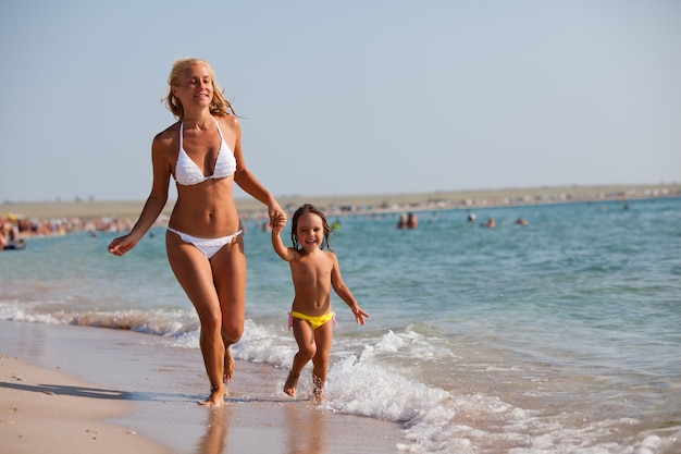 Jonge blonde moeder in blauwe bikini en haar kleine dochter die op de rand van het zeewater in zonneschijn lopen en op zomerdag glimlachen
