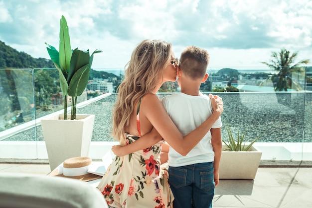 Jonge blonde moeder kust haar zoon. familie vakantie.