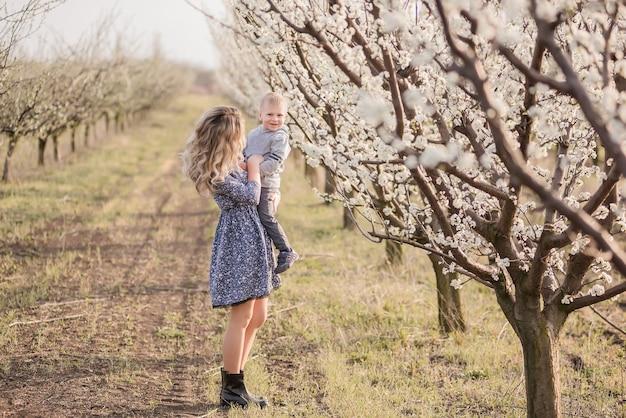 Jonge blonde moeder met haar zoontje loopt aan de hand tussen de bloeiende appelboomgaarden