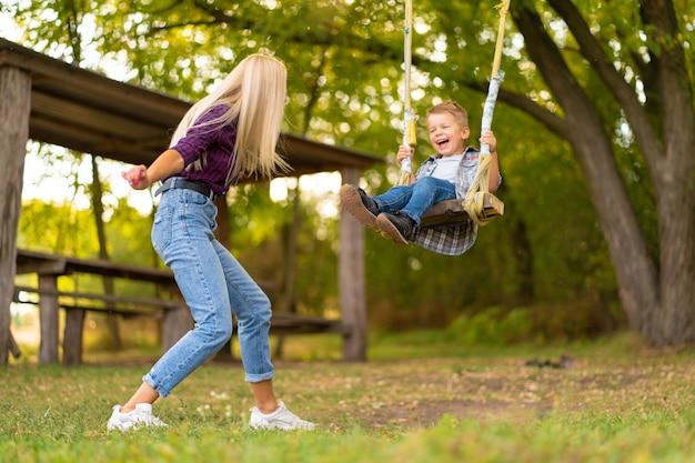 Jonge blonde moeder schudt haar zoontje op een schommel in een groen park. gelukkige jeugd.