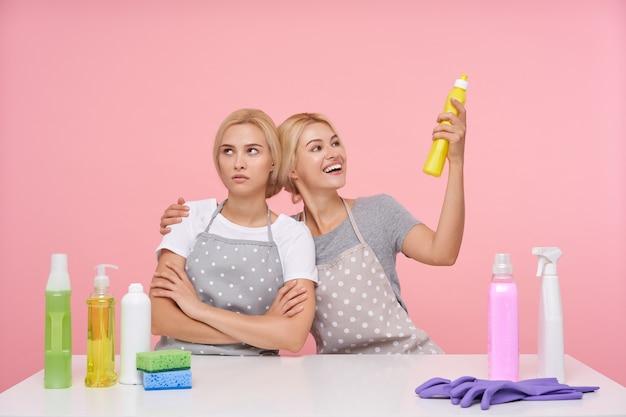 Jonge blonde mooie huisvrouwen dragen rubberen handschoenen tijdens de voorbereiding op de voorjaarsschoonmaak