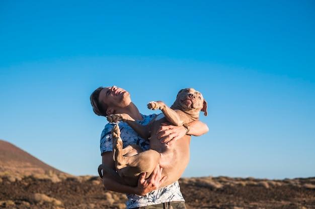 Jonge blonde mooie man en zijn geliefde hond hebben veel plezier samen lachen en glimlachen in vrijetijdsbesteding buitenshuis