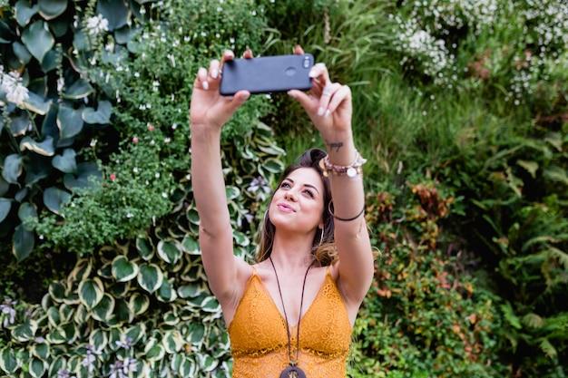 Jonge blonde mooie vrouw bij de straat die een beeld met mobiele telefoon en het glimlachen neemt. zomer, groene achtergrond