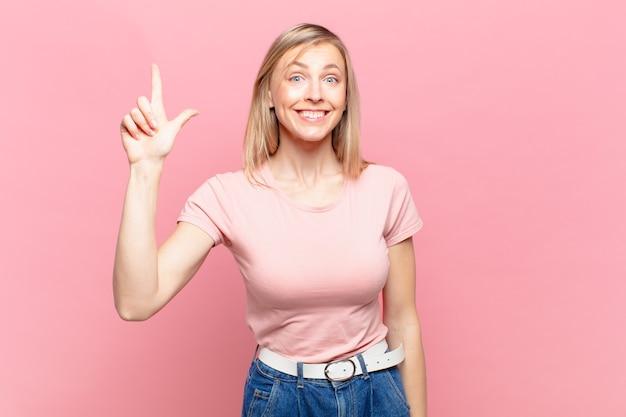 Jonge blonde mooie vrouw die vrolijk en gelukkig glimlacht, naar boven wijst met één hand om ruimte te kopiëren