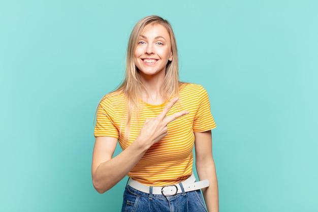 Jonge blonde mooie vrouw die zich gelukkig, positief en succesvol voelt, met de hand die een v-vorm over de borst maakt, overwinning of vrede toont