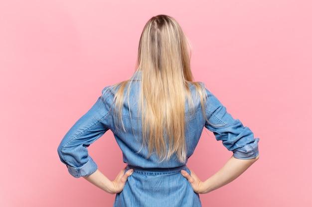 Jonge blonde mooie vrouw die zich verward of vol voelt of twijfels en vragen, zich afvragend, met de handen op de heupen, achteraanzicht