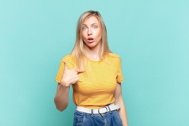 Jonge blonde mooie vrouw die zich verward, verbaasd en onzeker voelt, wijzend naar zichzelf en zich afvragend wie, ik?