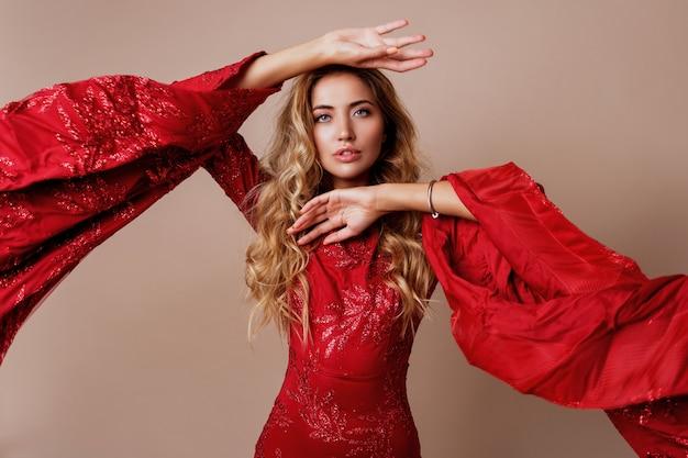Jonge blonde mooie vrouw in luxe rode jurk met wijde mouwen. expressieve houding.