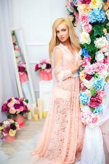 Jonge blonde mooie vrouw in romantische negligetribune dichtbij bed dat met bloemen wordt verfraaid