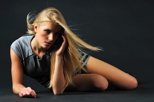 Jonge blonde mooie vrouw in zwarte jurk en schoenen zittend op de vloer over donkere muur op foto. schoonheid en mode levensstijl concept