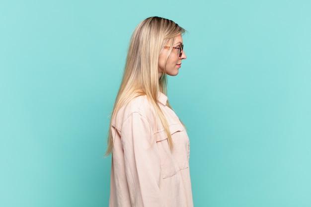 Jonge blonde mooie vrouw op profielweergave die ruimte vooruit wil kopiëren, denken, fantaseren of dagdromen