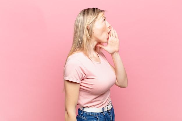 Jonge blonde mooie vrouw profielweergave, blij en opgewonden kijkend, schreeuwend en bellend om ruimte aan de zijkant te kopiëren