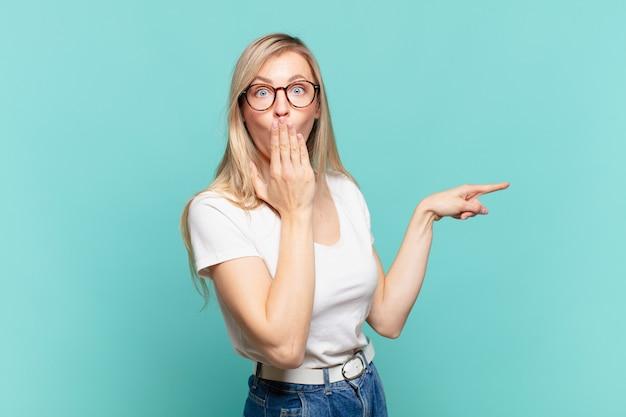Jonge blonde mooie vrouw voelt zich gelukkig, geschokt en verrast, bedekt de mond met de hand en wijst naar de laterale kopieerruimte