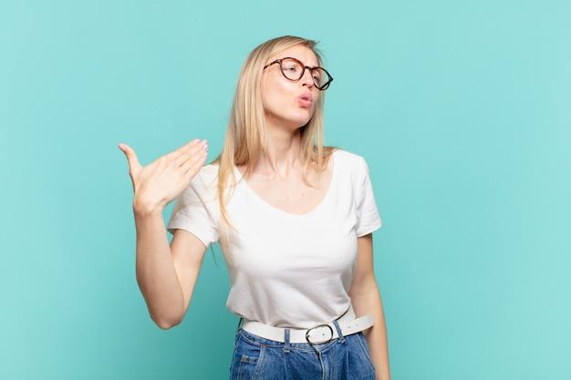 Jonge blonde mooie vrouw voelt zich gestrest, angstig, moe en gefrustreerd, trekt aan de nek van het shirt, ziet er gefrustreerd uit met problemen