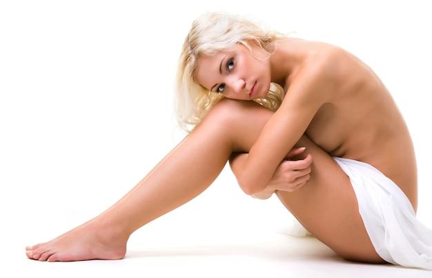 Jonge blonde naakte vrouw zitten en omhelzen haar benen met handen op witte achtergrond in fotostudio. schoonheid van het lichaam van de vrouw, het gezondheidsconcept van de vrouw