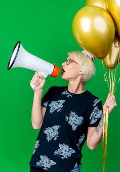 Jonge blonde partij meisje bril en verjaardag glb bedrijf ballonnen draaien hoofd naar kant praten door spreker geïsoleerd op groene achtergrond