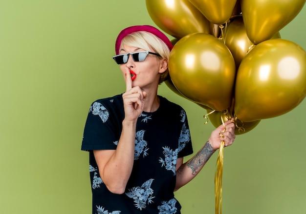 Jonge blonde partijvrouw die partijhoed en zonnebril draagt die ballons houdt die stiltegebaar doen dat op olijfgroene muur met exemplaarruimte wordt geïsoleerd