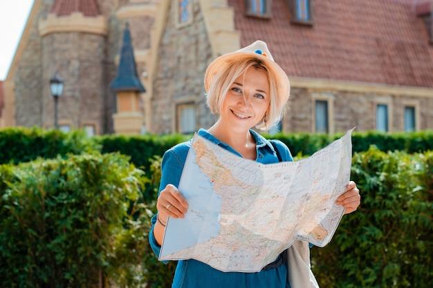 Jonge blonde reiziger vrouw in een hoed en zonnebril met een kaart
