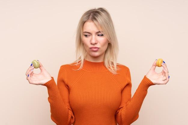 Jonge blonde russische vrouw die over geïsoleerde muur kleurrijke franse macarons houden en ongelukkig