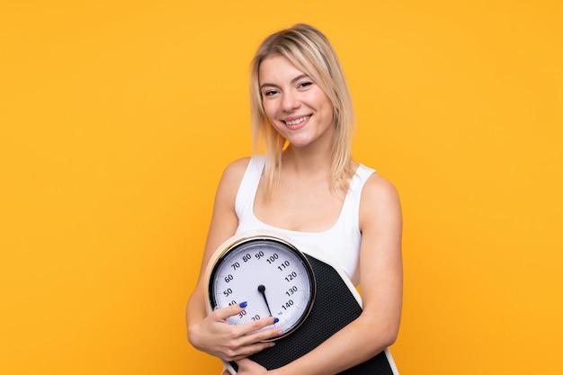 Jonge blonde russische vrouw over geïsoleerde gele muur met weegmachine
