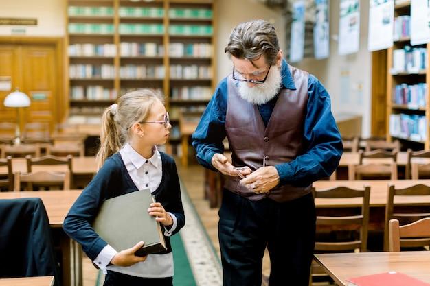 Jonge blonde schoolmeisje in glazen, boek in handen houden, knappe bejaarde bebaarde man bibliothecaris vragen over sommige boeken