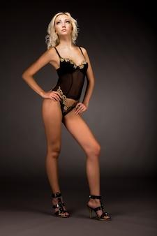 Jonge blonde slanke vrouw in sexy zwarte lingerie en schoenen met hoge hakken permanent over donkere achtergrond in fotostudio. schoonheid van het vrouwenlichaam en stijlvol ondergoedconcept