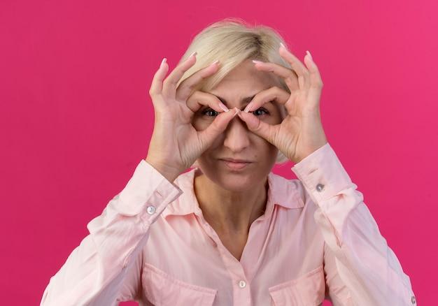 Jonge blonde slavische vrouw die camera bekijkt en blikgebaar doet die handen als verrekijker gebruikt die op roze achtergrond wordt geïsoleerd