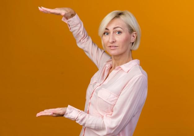 Jonge blonde slavische vrouw die grootte toont