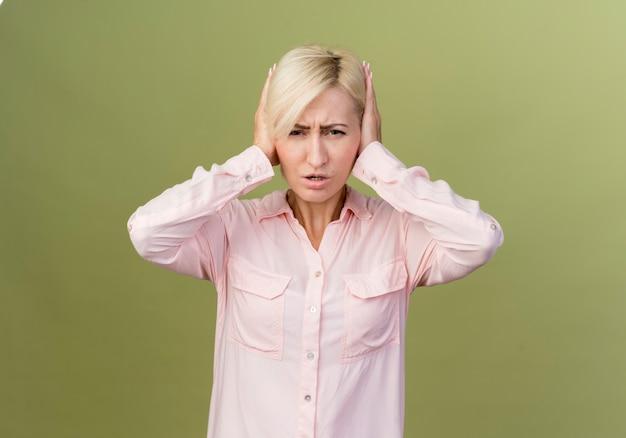 Jonge blonde slavische vrouw die haar oren bedekt met handen