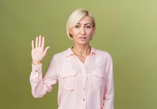 Jonge blonde slavische vrouw die hallo gebaar toont