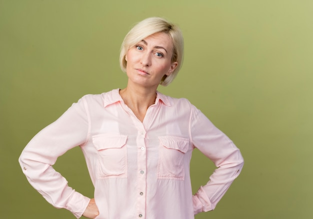 Jonge blonde slavische vrouw die handen op de heupen zet die op olijfgroene muur worden geïsoleerd
