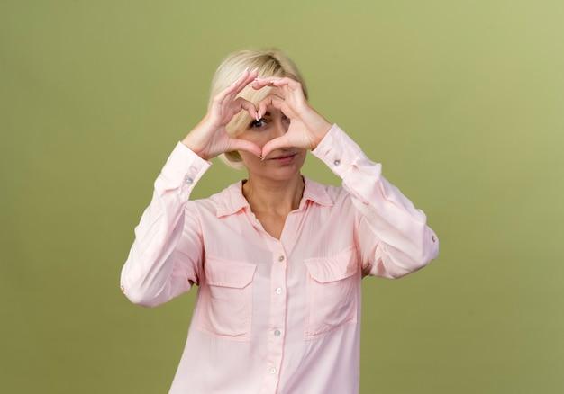 Jonge blonde slavische vrouw die hartgebaar toont dat op olijfgroen wordt geïsoleerd