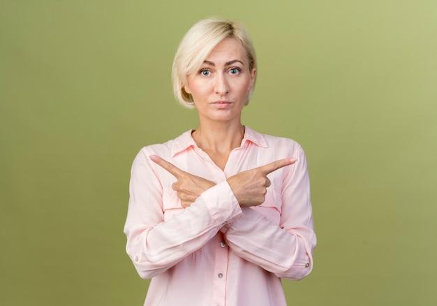 Jonge blonde slavische vrouw wijst in een andere richting
