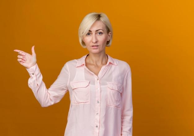 Jonge blonde slavische vrouw wijst naar de zijkant